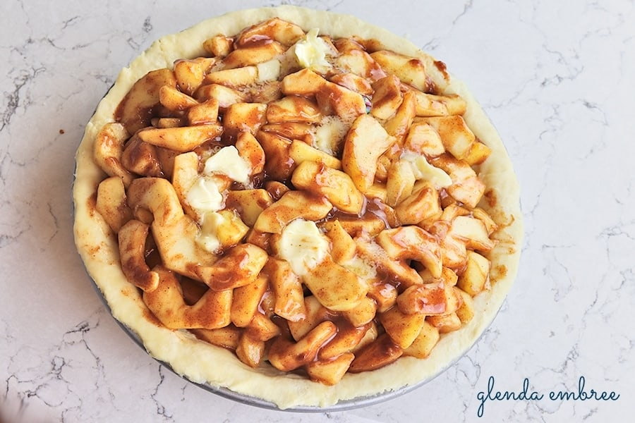 homemade apple pie filling mounded into unbaked bottom pie crust and dotted with butter