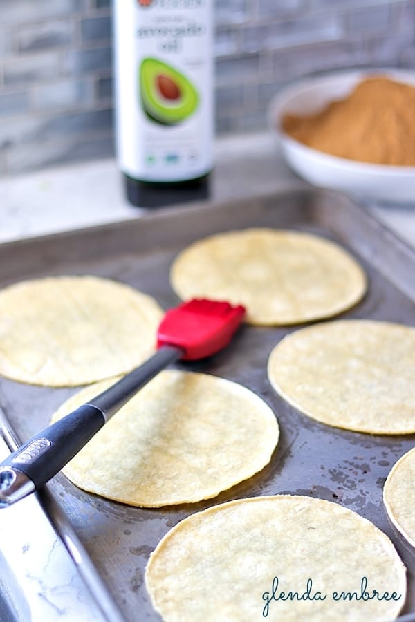 Brushing corn tortillas with oil to make taco chips.