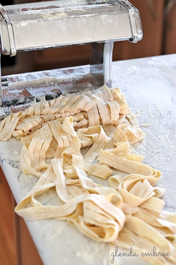 cutting homemade pasta with a pasta machine