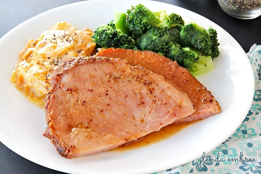 Best slow cooker ham served with cheesy scalloped potatoes and steamed broccoli