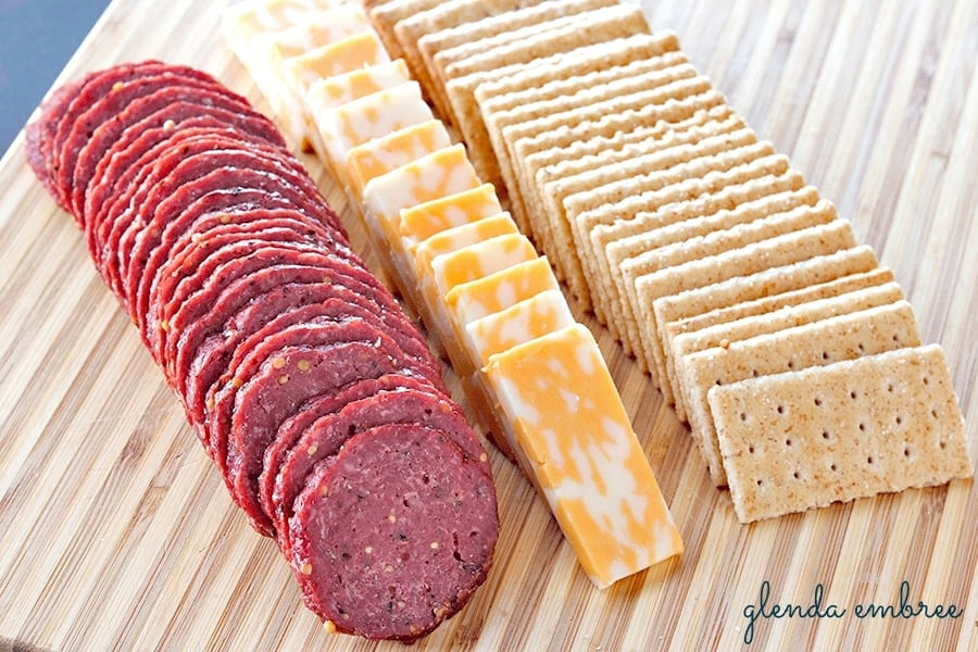 Homemade Beef Summer Sausage on wooden board with marble jack cheese and whole grain crackers