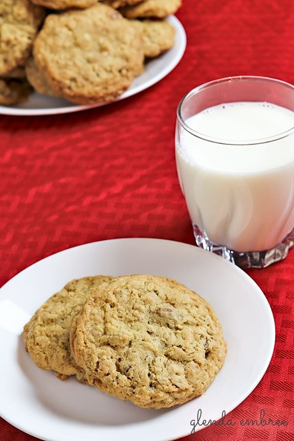 oatmeal cookies on a dessert plate with a glass of milk on the side