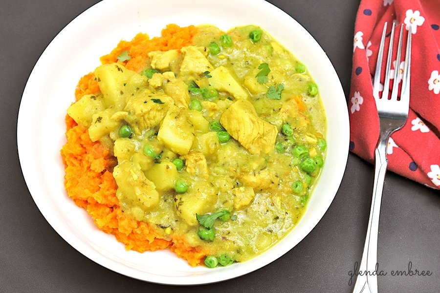 Yellow Chicken Curry with Potatoes and Peas over mashed sweet potatoes