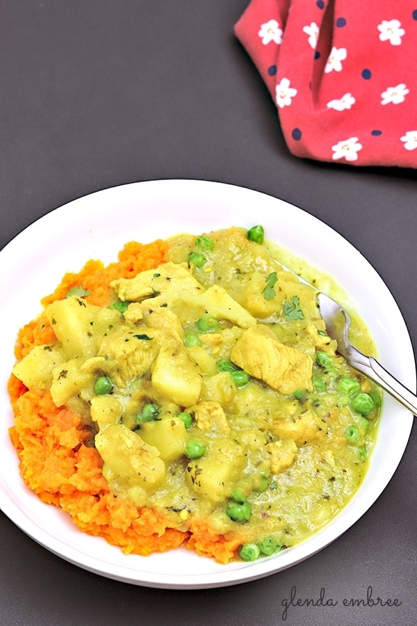 Yellow Chicken Curry with Potatoes and Peas served over sweet potatoes
