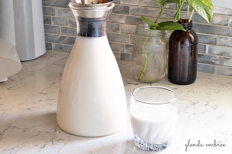 Cashew Coconut Milk in a glass bottle with a glass of Cashew Coconut Milk on the side. Fabulous dairy alternative and non-dairy blend.