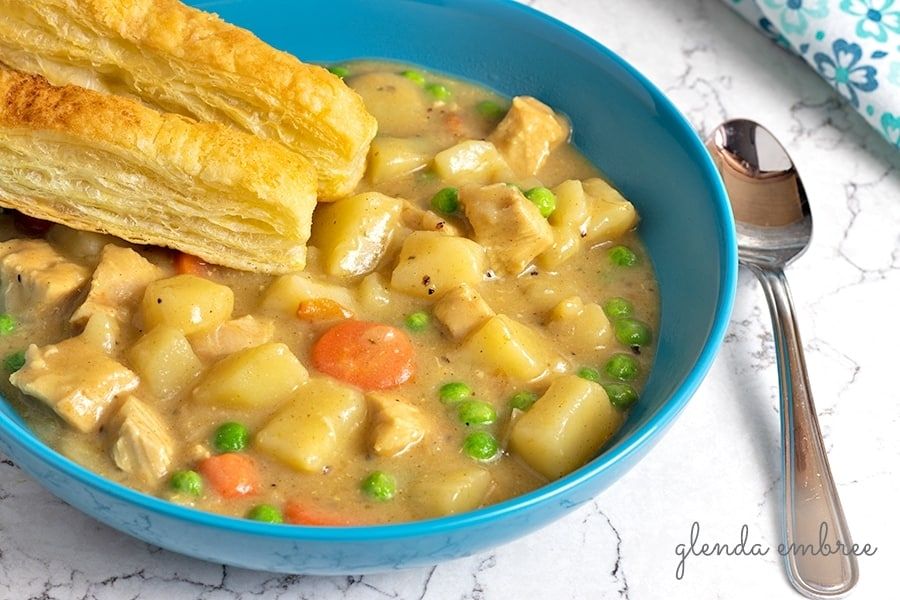 chicken pot pie soup in a bowl with puff pastry sticks