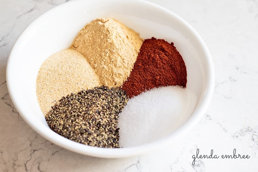 bowl with herbs and spices to make best all purpose seasoning blend. Bowl includes garlic powder, onion powder, parika, salt and pepper.