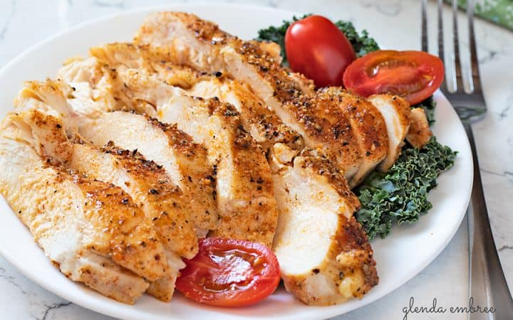 perfect baked chicken breasts sliced and served on a white plate with kale and grape tomatoes