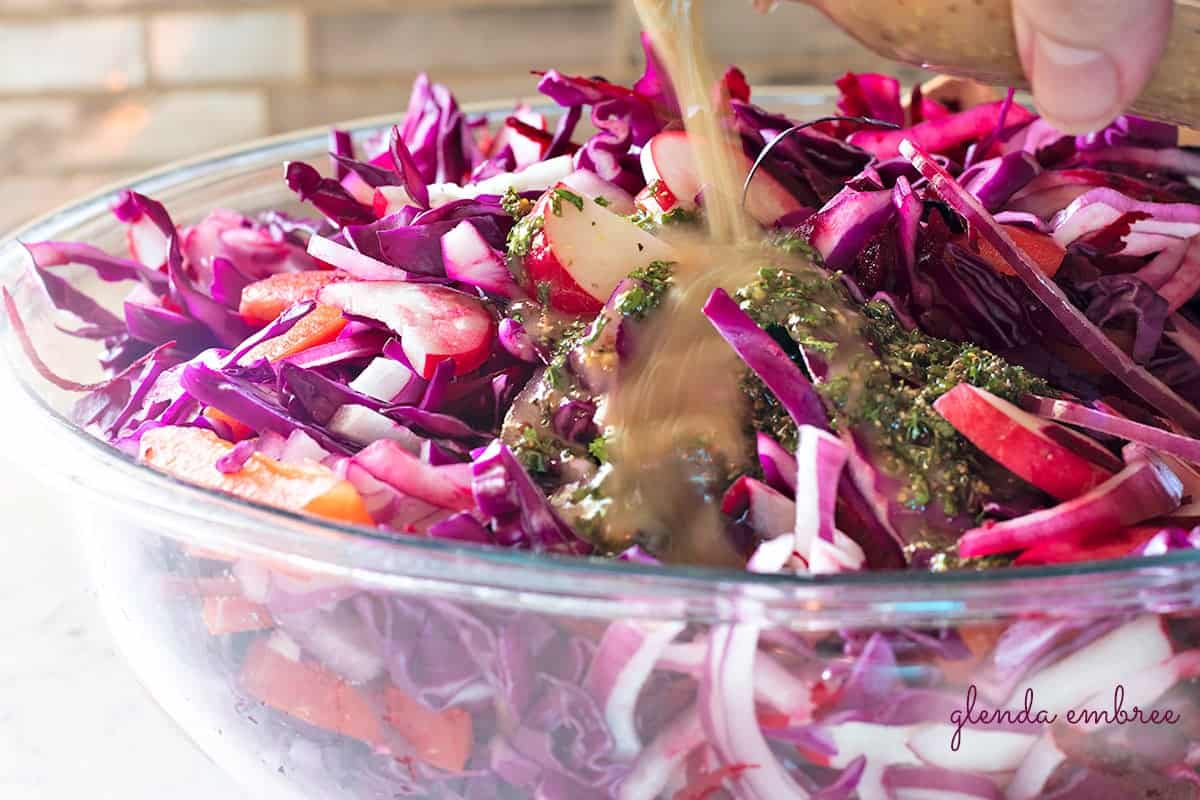 Pouring dressing over Ruby Coleslaw