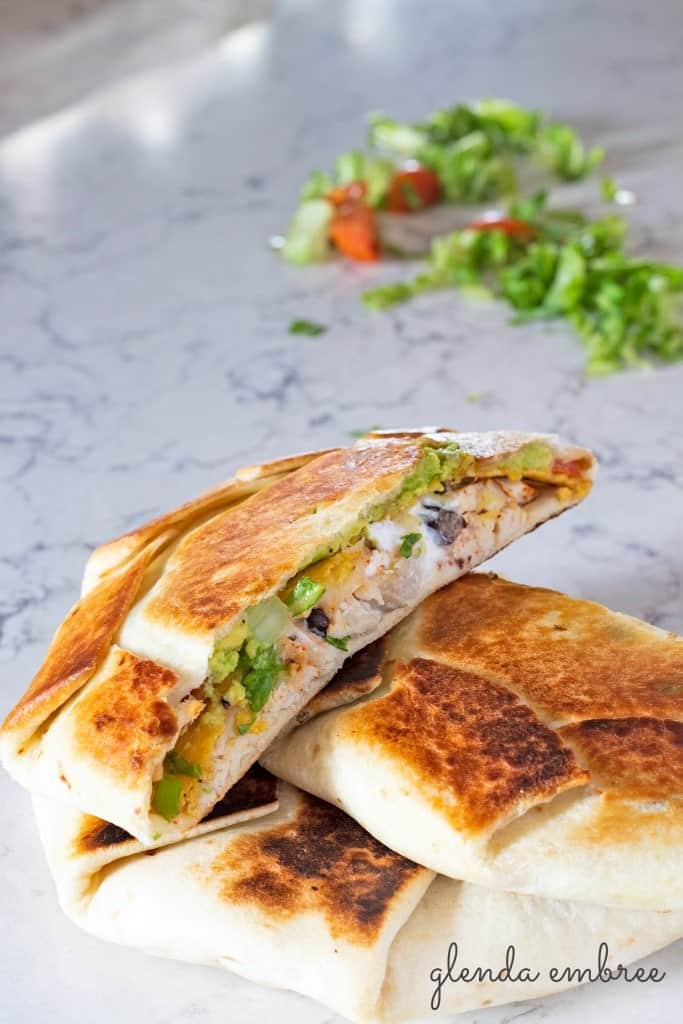 Chicken Crunch wrap supreme cut in half and resting on a marble counter