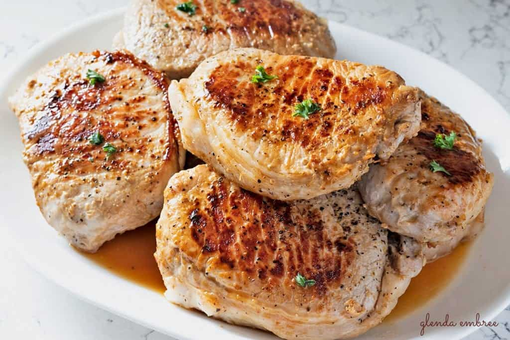 Perfect Pan Seared Pork Chops on a white serving platter