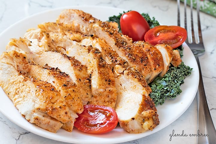 Perfect Baked Chicken Breasts served on a white plate with kale and cherry tomatoes.  Easy recipes that make homemade easy.