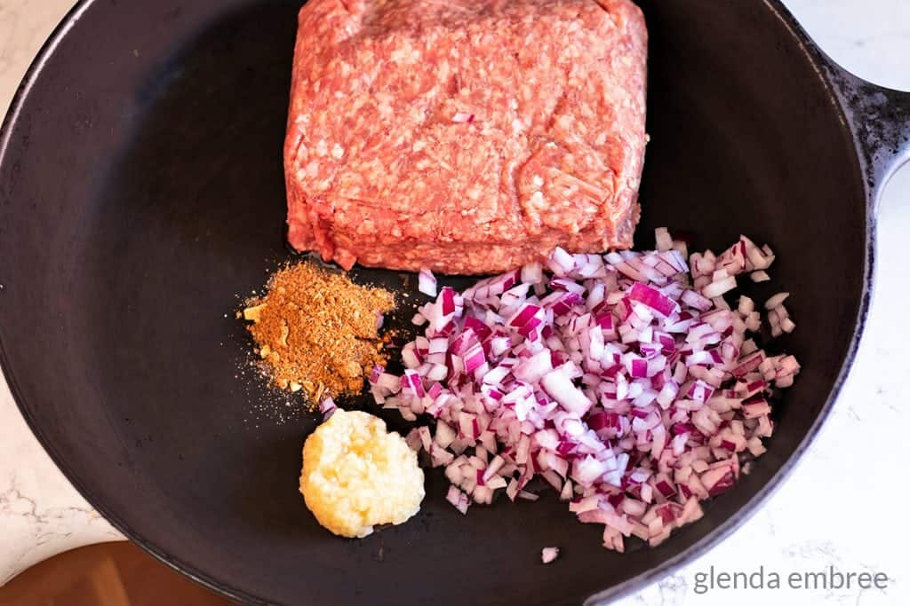 Ground beef, minced red onion, minced garlic and all purpose seasoning in a cast iron skillet.