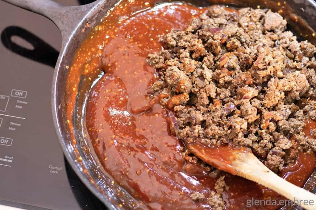 adding ground beef to homemade sloppy joe sauce in a cast iron skillet